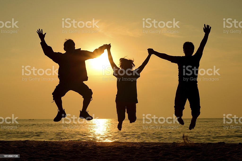 Silhouette Group of happy people  jumping on the beach royalty-free stock photo
