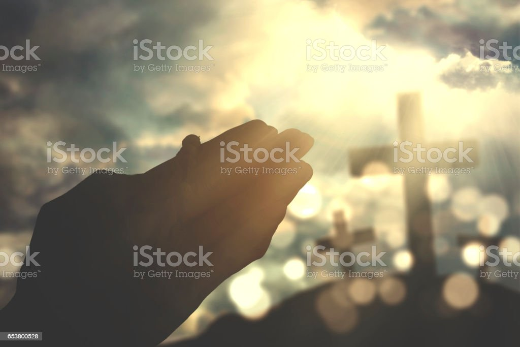 Silhouette hands praying with rosary stock photo