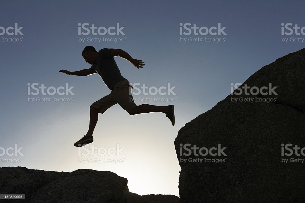 Silhouette image of a man jumping from cliff royalty-free stock photo