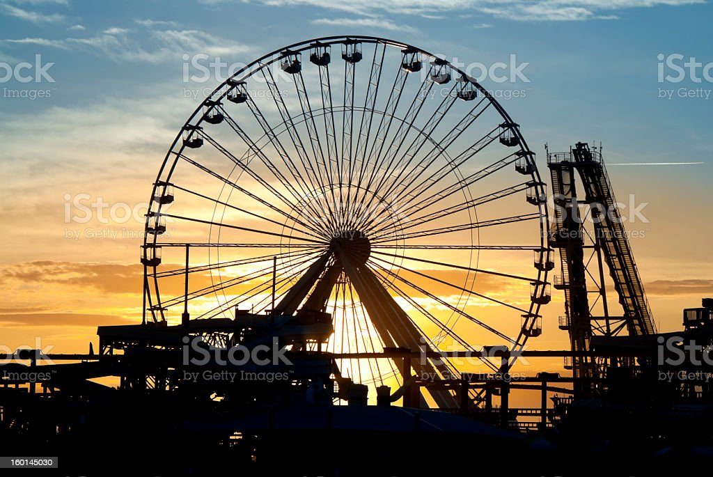 Silhouette image of an amusement park at sunset stock photo