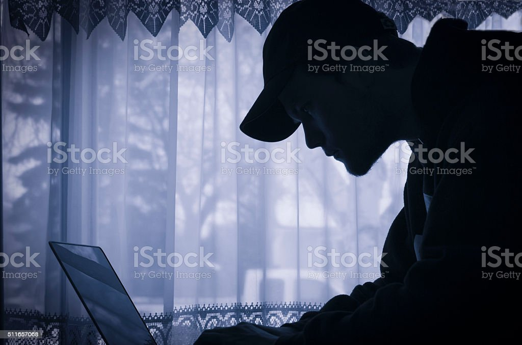 silhouette image of young man on his laptop. stock photo