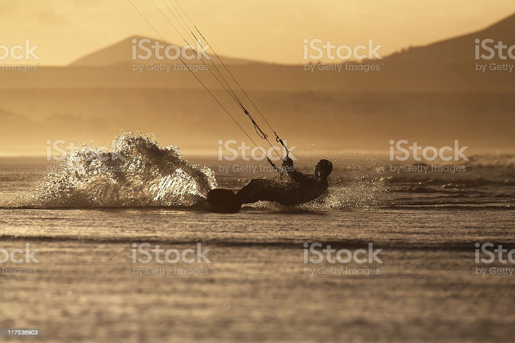 silhouette kitesurfer / kiteboarder scratching the waters surface stock photo