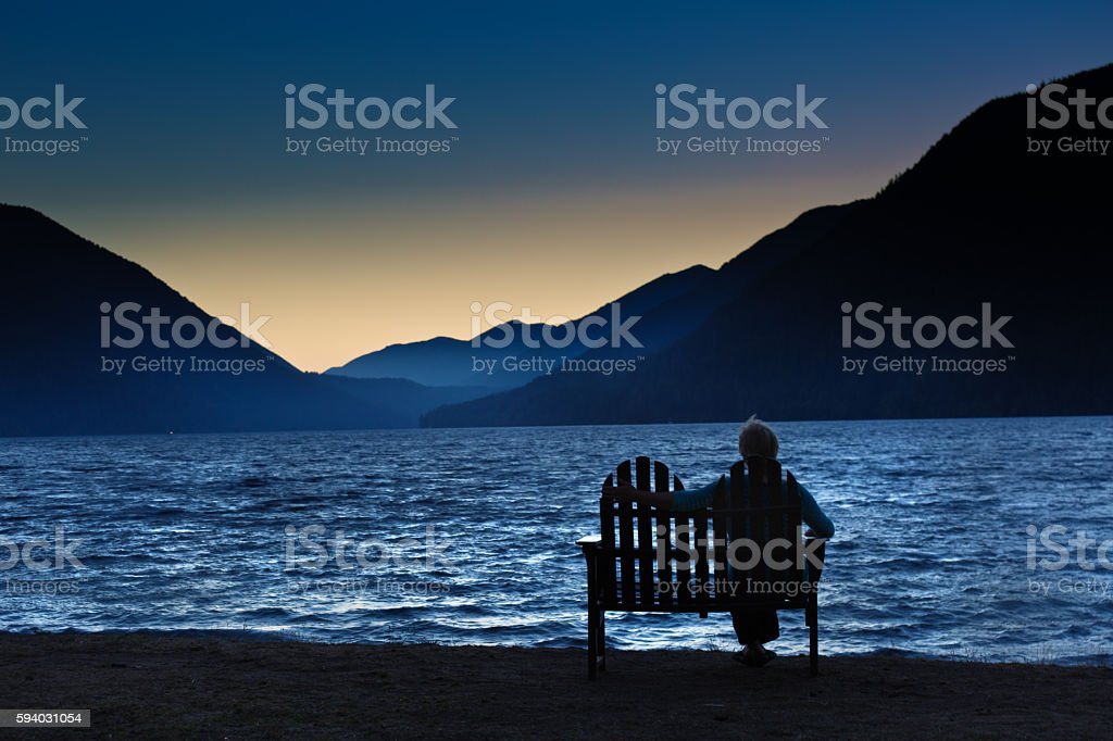 Silhouette Lonely Woman Sitting Watching the Sunrise stock photo
