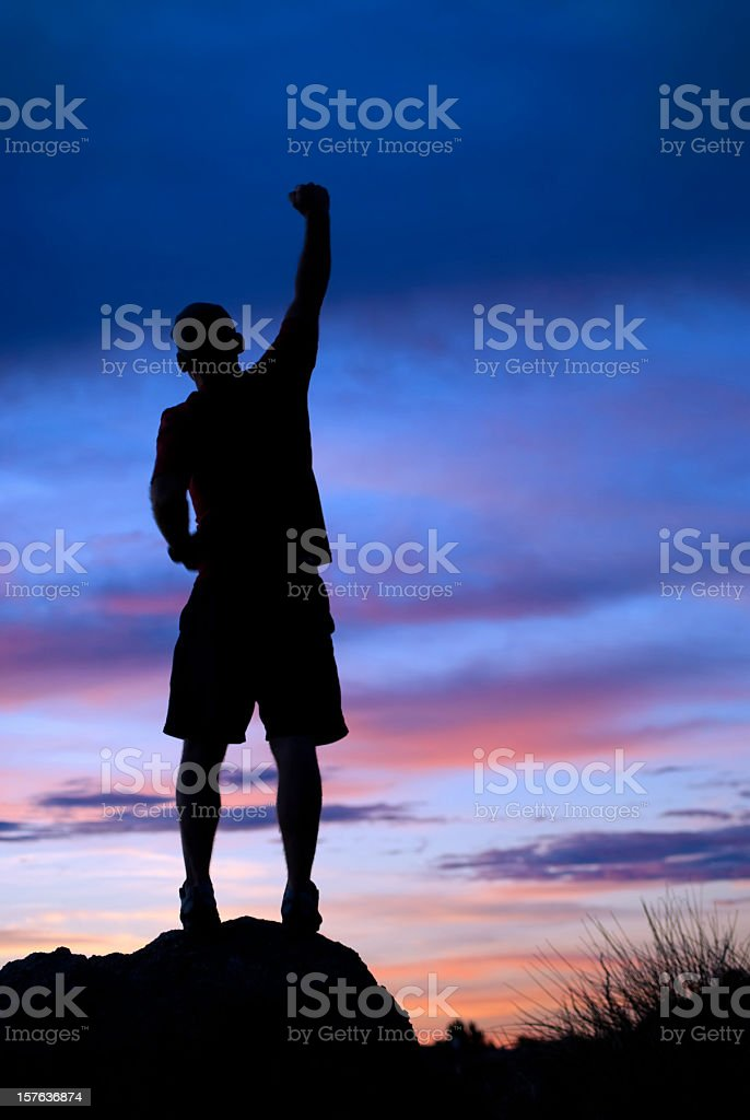 silhouette man arm raised into sunset sky royalty-free stock photo