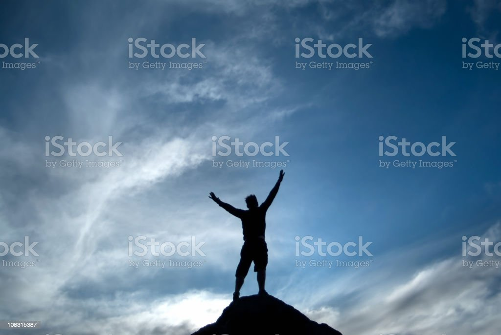 silhouette man arms raised into sky abstract royalty-free stock photo
