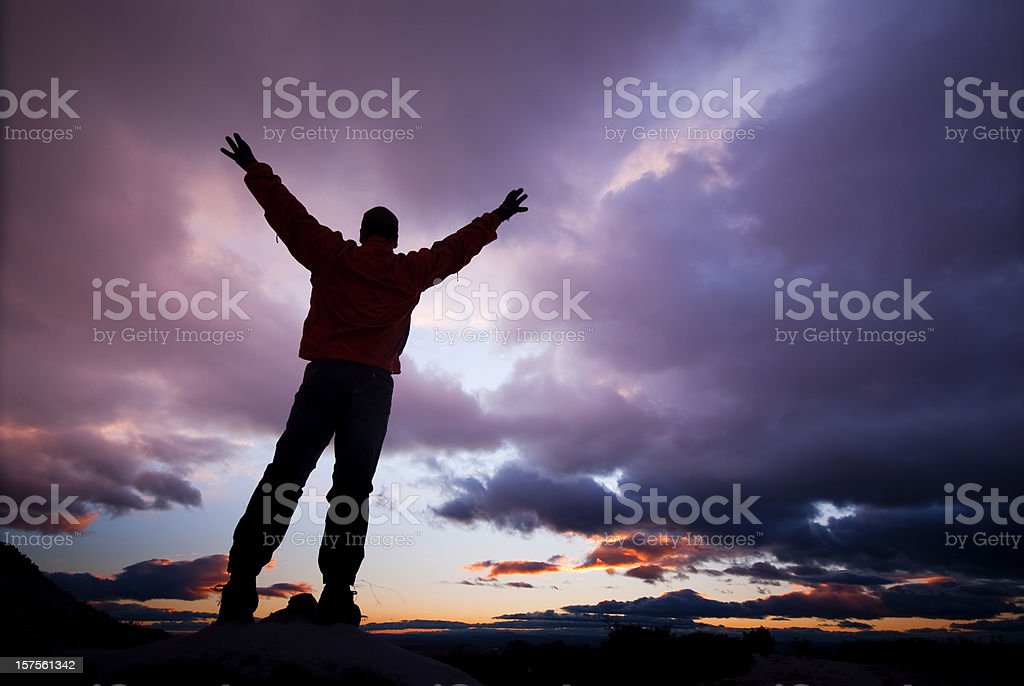silhouette man arms raised into sunset sky clouds royalty-free stock photo