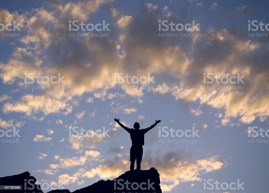silhouette man sunset arms raised to the sky royalty-free stock photo