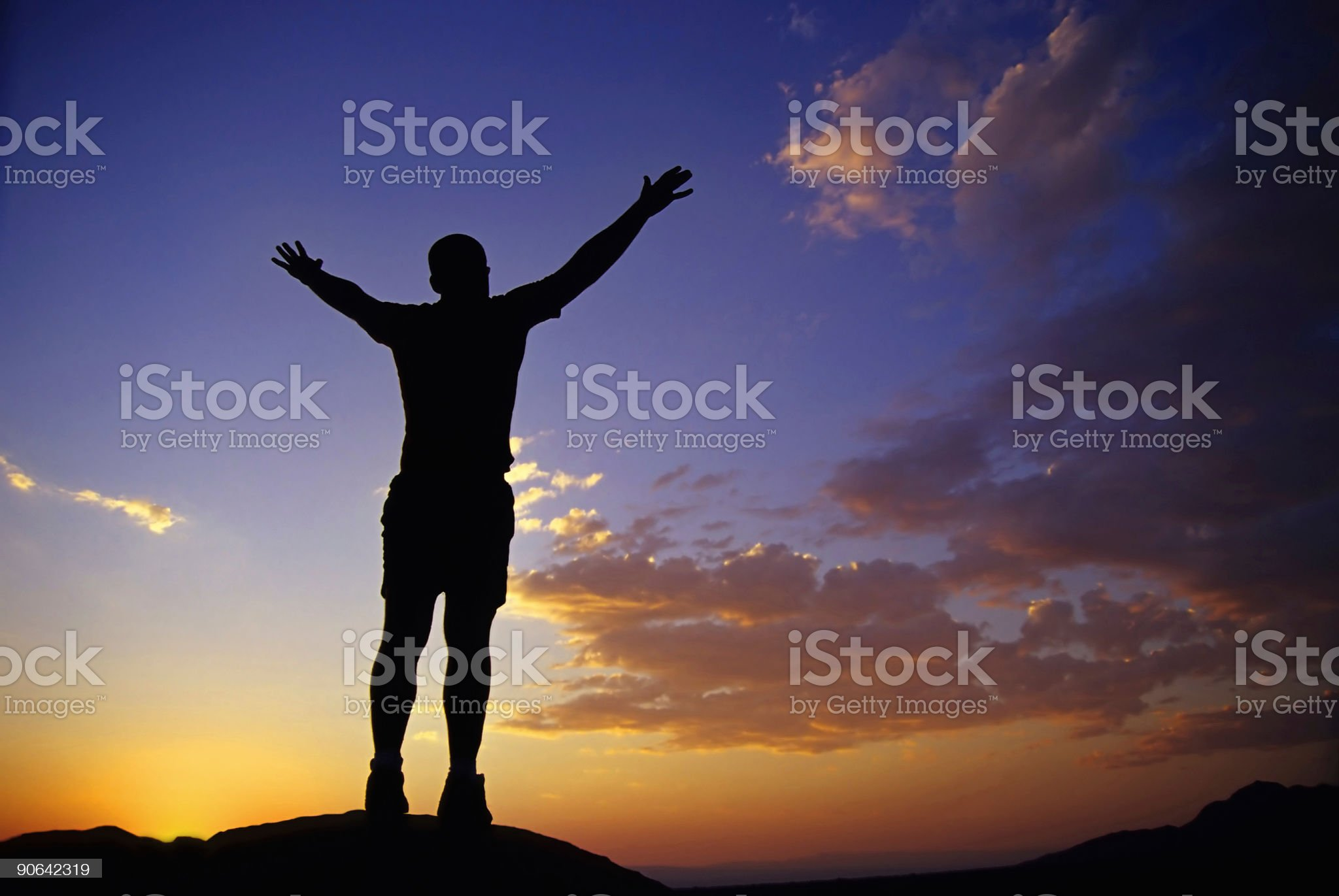 silhouette man with arms raised into sunset sky landscape royalty-free stock photo