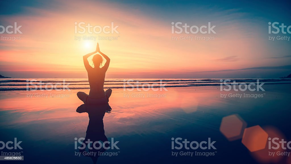 Silhouette meditation girl on background of the sea and sunset stock photo