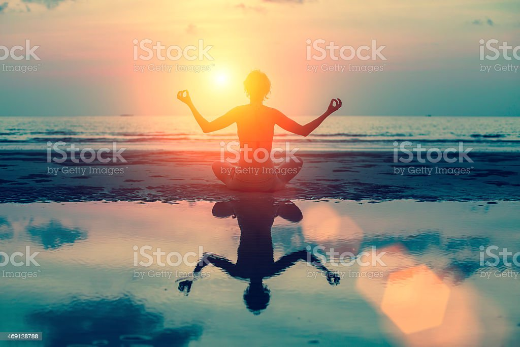 Silhouette meditation girl on the background of sea and sunset. stock photo