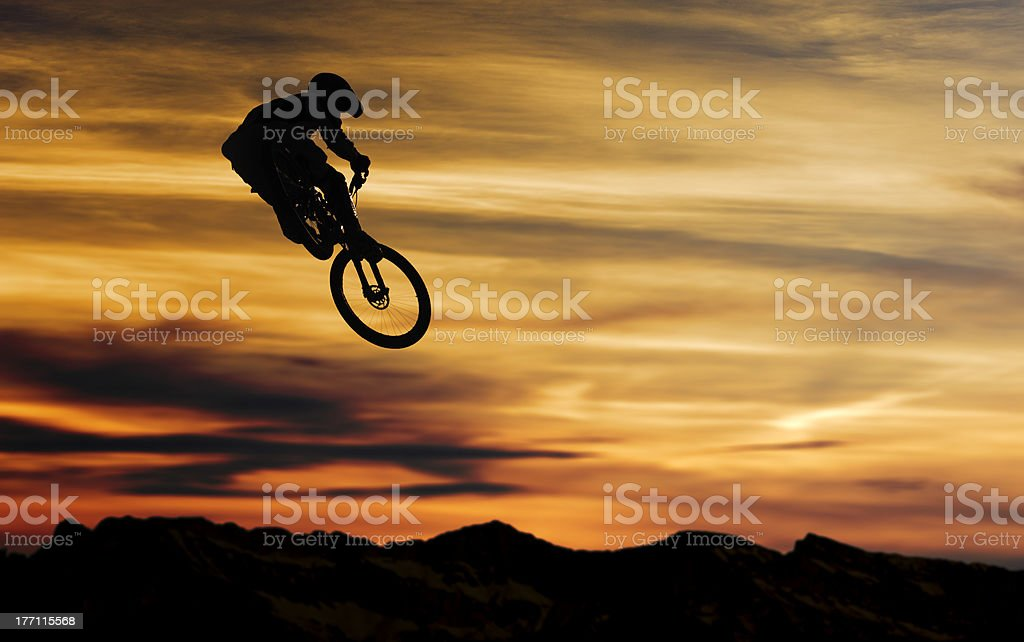 Silhouette mountain bike rider jumping at sunset stock photo