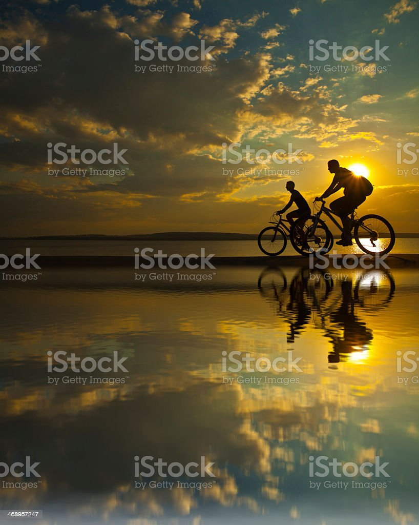 Silhouette of 2 cyclists during sunset with their reflection stock photo