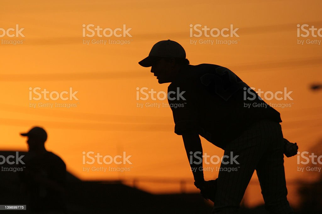Silhouette of a baseball pitcher about to throw at sunset stock photo