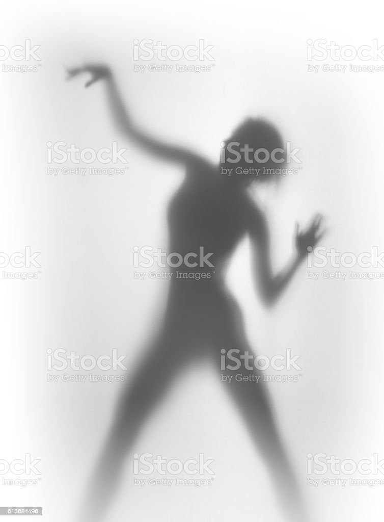 Silhouette of a beautiful and sexy dancing woman stock photo