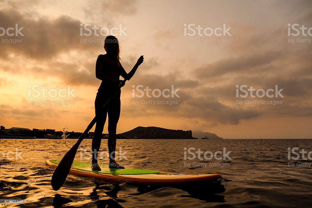 Silhouette of a beautiful woman on Stand Up Paddle Board. stock photo
