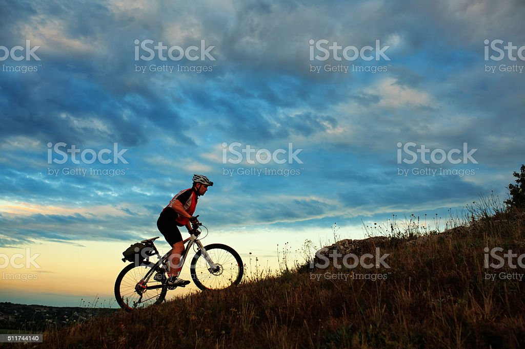 Silhouette of a biker and bicycle on sky background stock photo