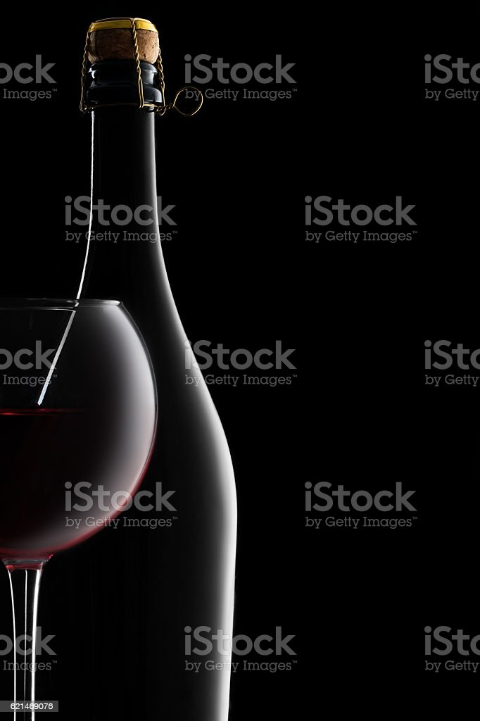 Silhouette of a Bottle and Red Wine Glass stock photo