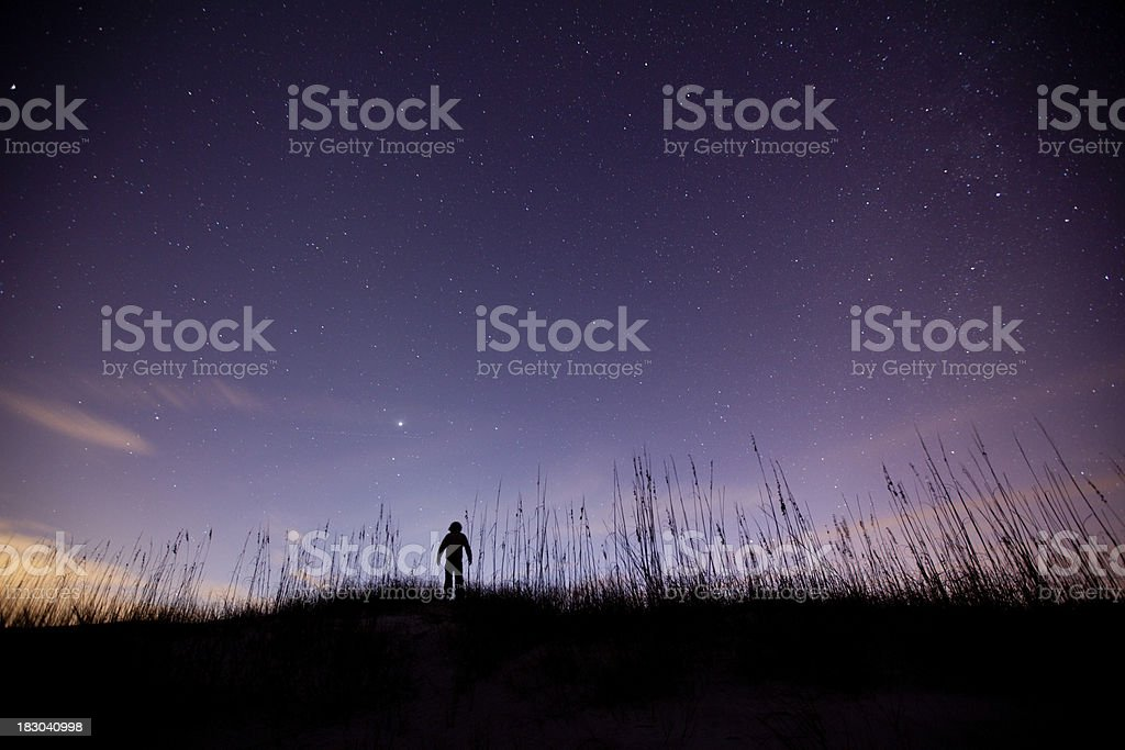 Silhouette of a boy admiring the purple sky. royalty-free stock photo