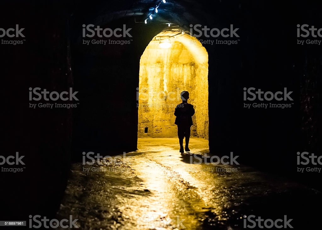 Silhouette of a boy in a dark tunnel stock photo