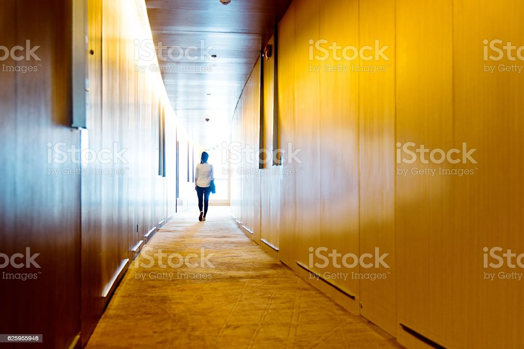 Silhouette of a businesswoman walking into the light stock photo