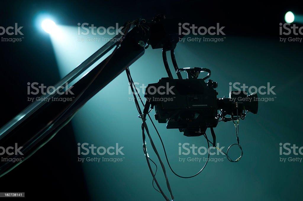 A silhouette of a camera crane in a spotlight stock photo