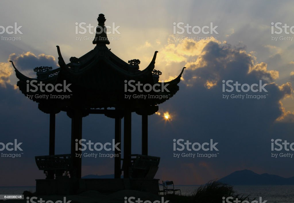 Silhouette of a Chinese pavilion on the shore at sunrise stock photo