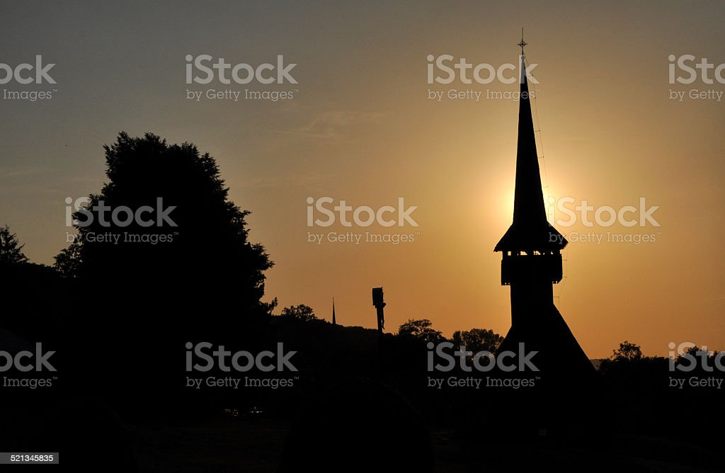 Silhouette of a church tower in the sunset stock photo