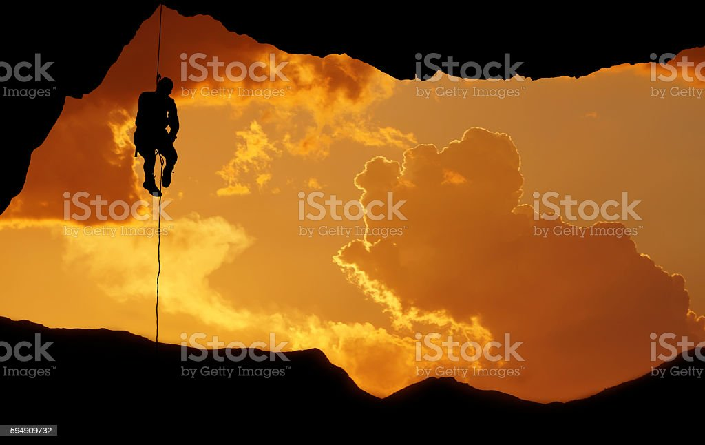 Silhouette of a climber over beautiful sunset stock photo