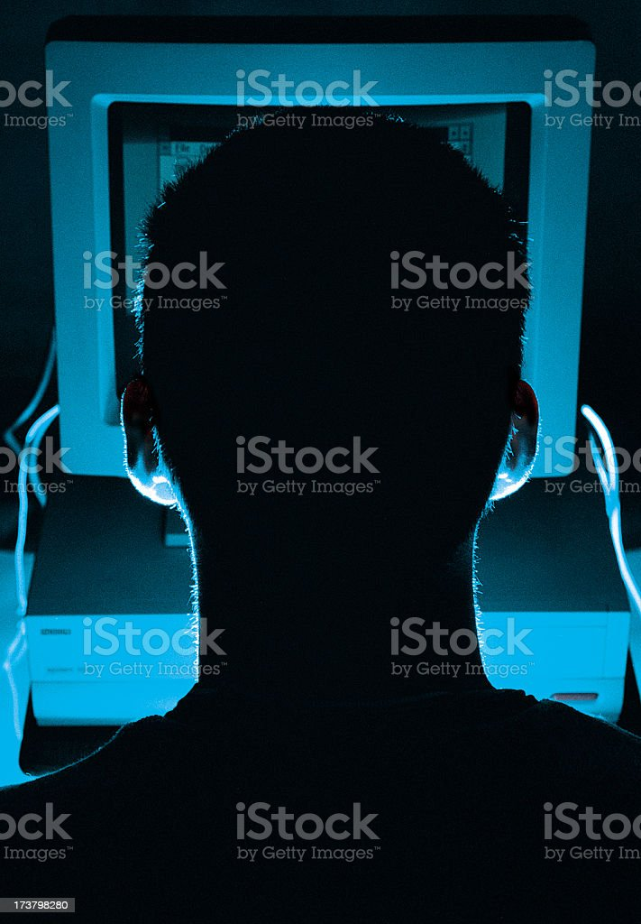 Silhouette of a computer hacker's head from behind screen stock photo