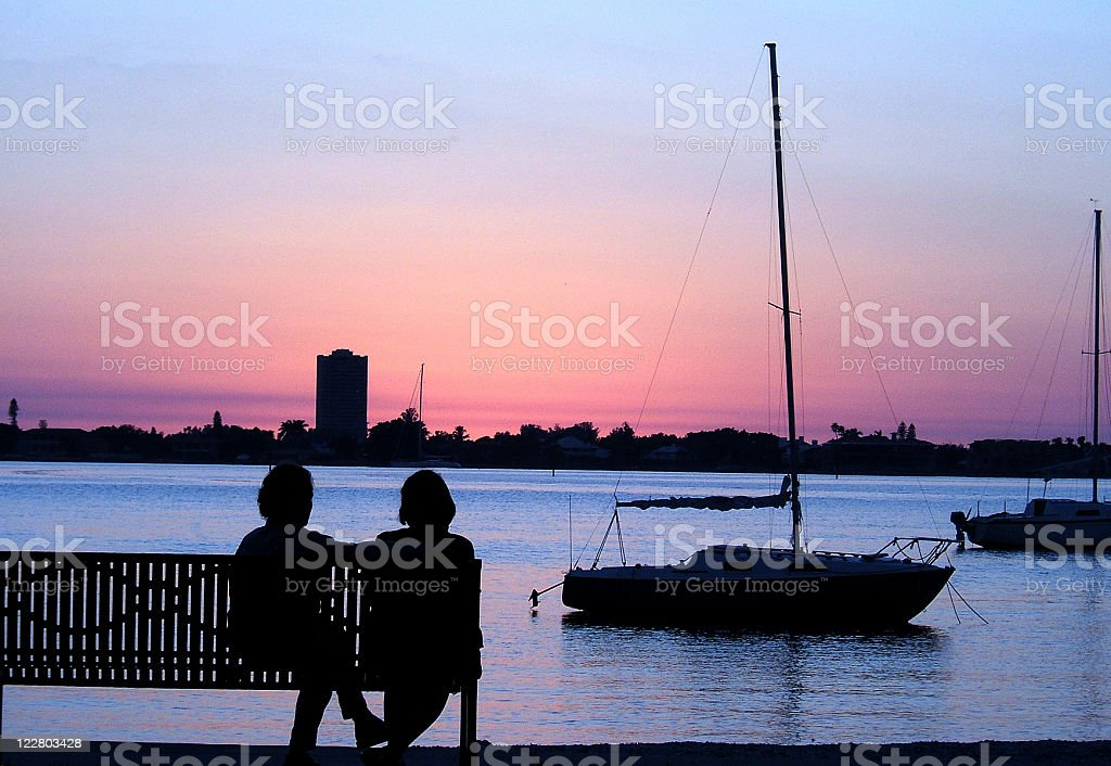A silhouette of a couple and boats stock photo
