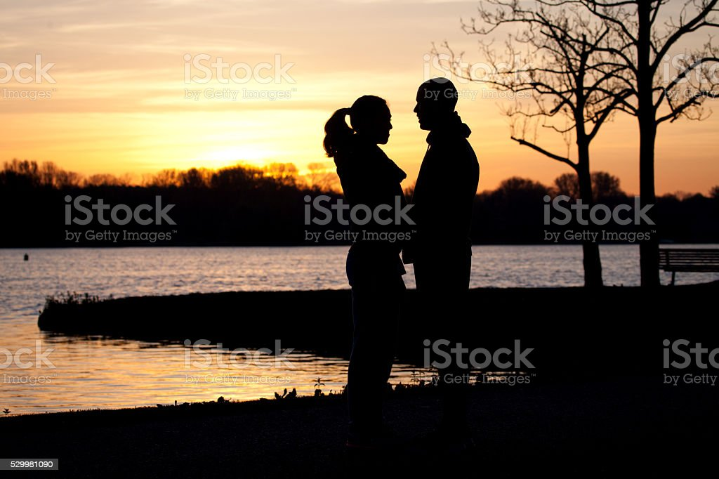 Silhouette of a couple at rural lakeside at dawn stock photo