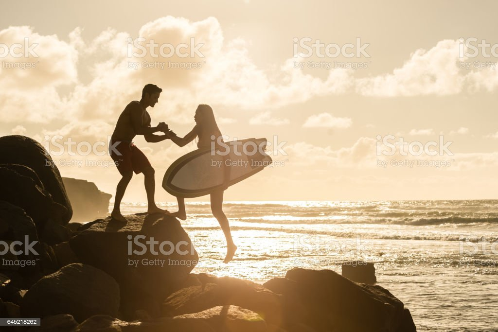 Silhouette of a Couple Helping With Their Surboards stock photo