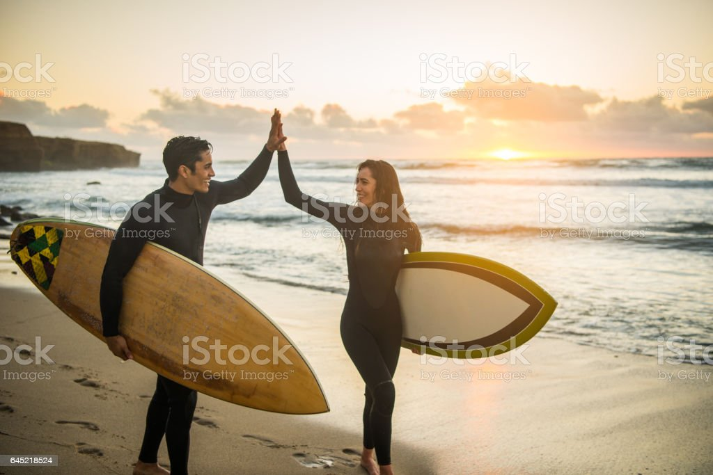 Silhouette of a Couple High Fiving With Their Surboards stock photo