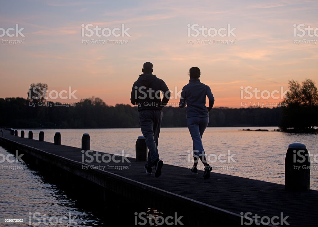 Silhouette of a couple running at dawn on a lake stock photo