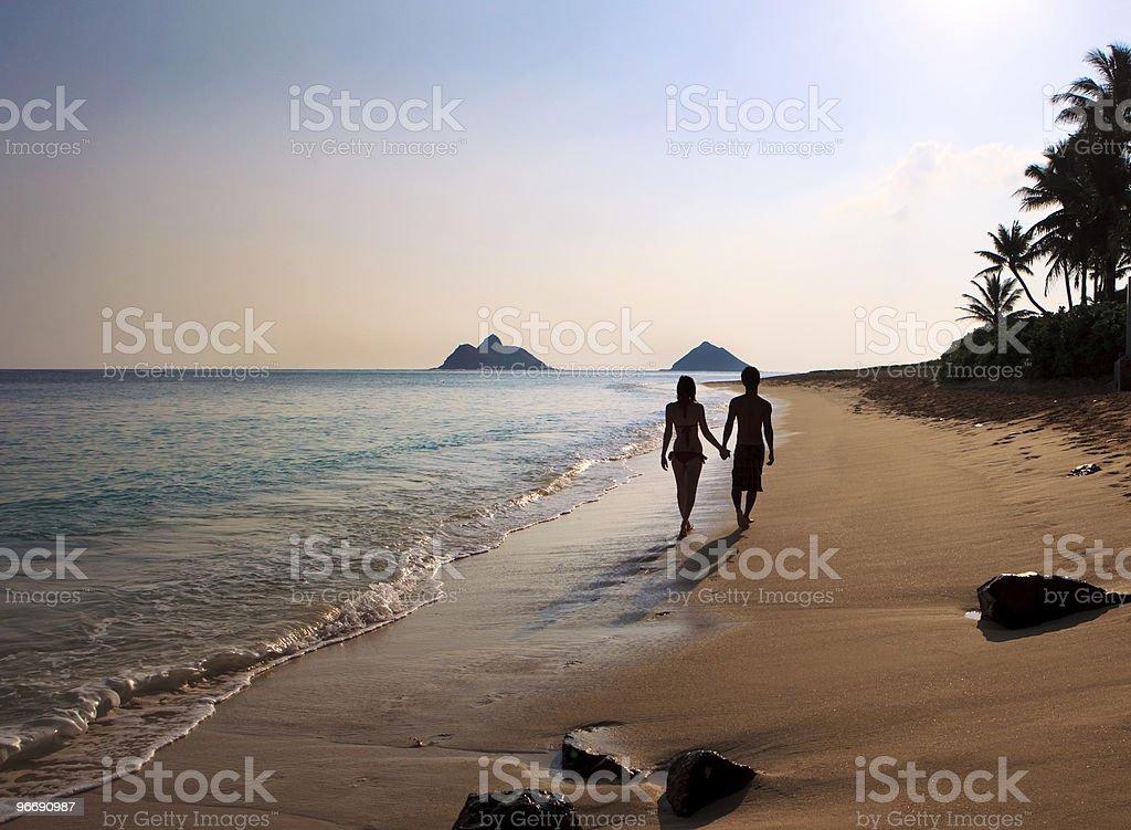 silhouette of a couple walking on lanikai beach stock photo
