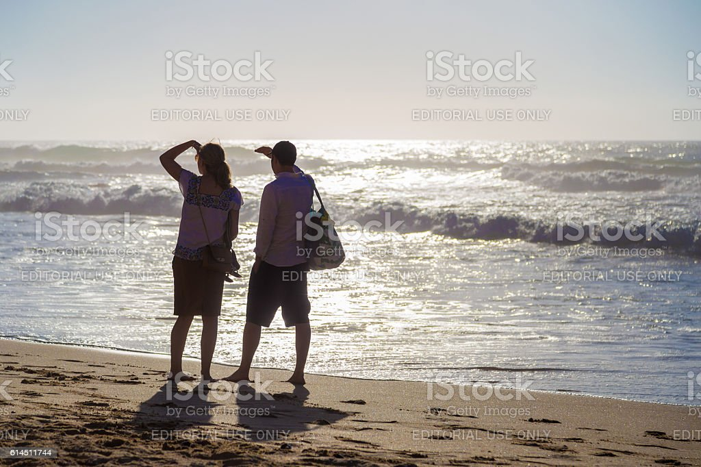 Silhouette of a couple watching at huge waves on Praia stock photo