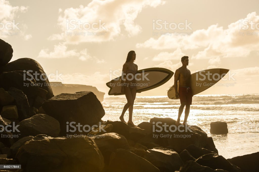 Silhouette of a Couple With Their Surboards stock photo