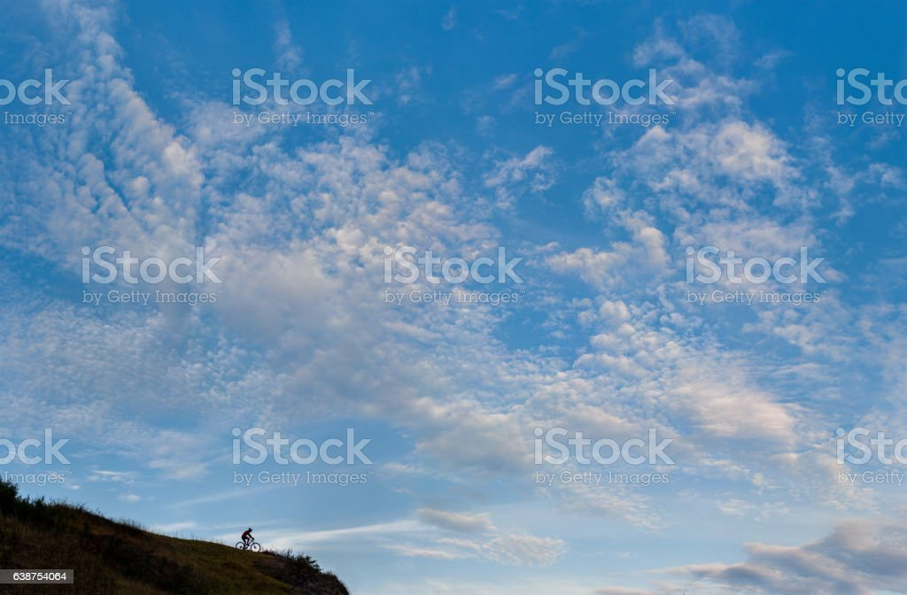 Silhouette of a cross country cyclist going downhill stock photo