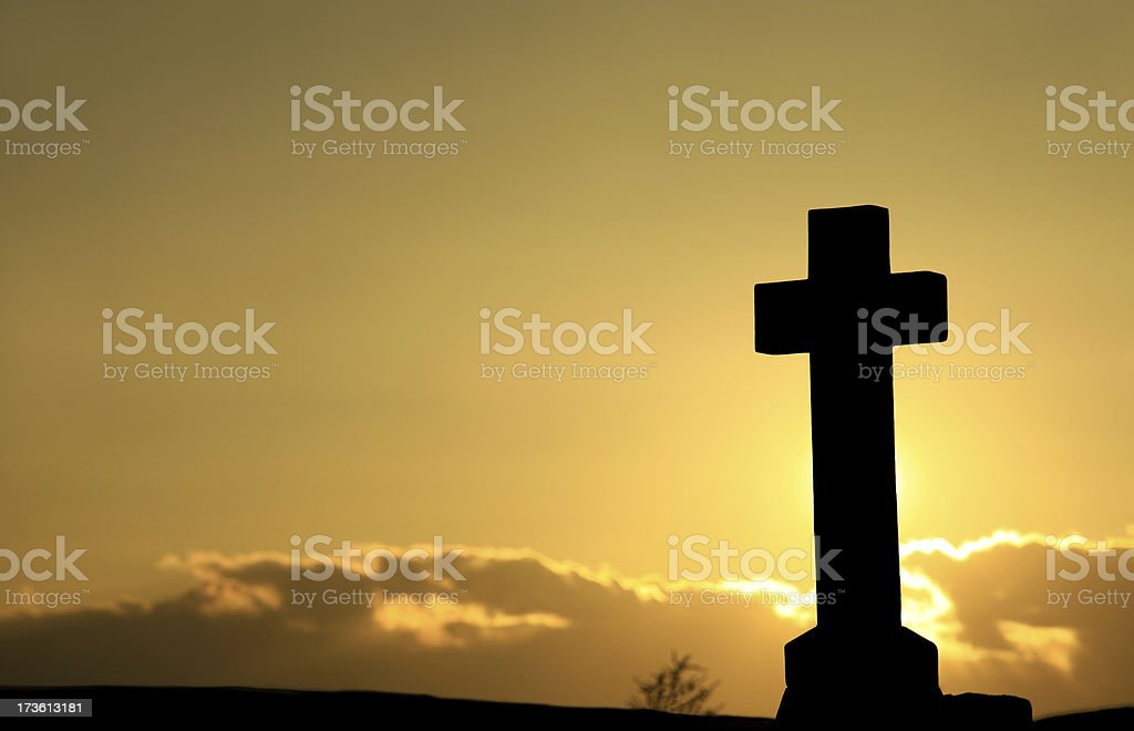 Silhouette of a cross in front of a cloudy sunset royalty-free stock photo