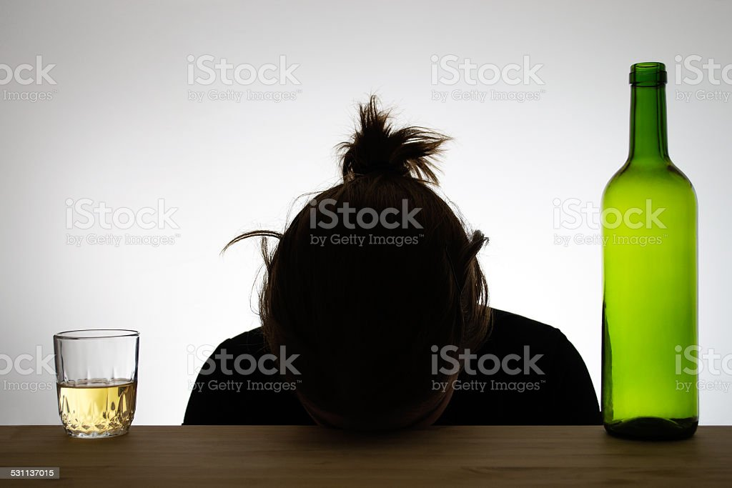 Silhouette of a drunk woman sleeping on a desk stock photo