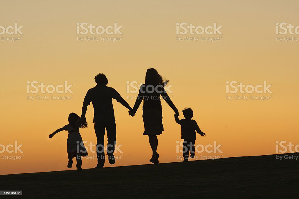 A silhouette of a family running into the sunset stock photo