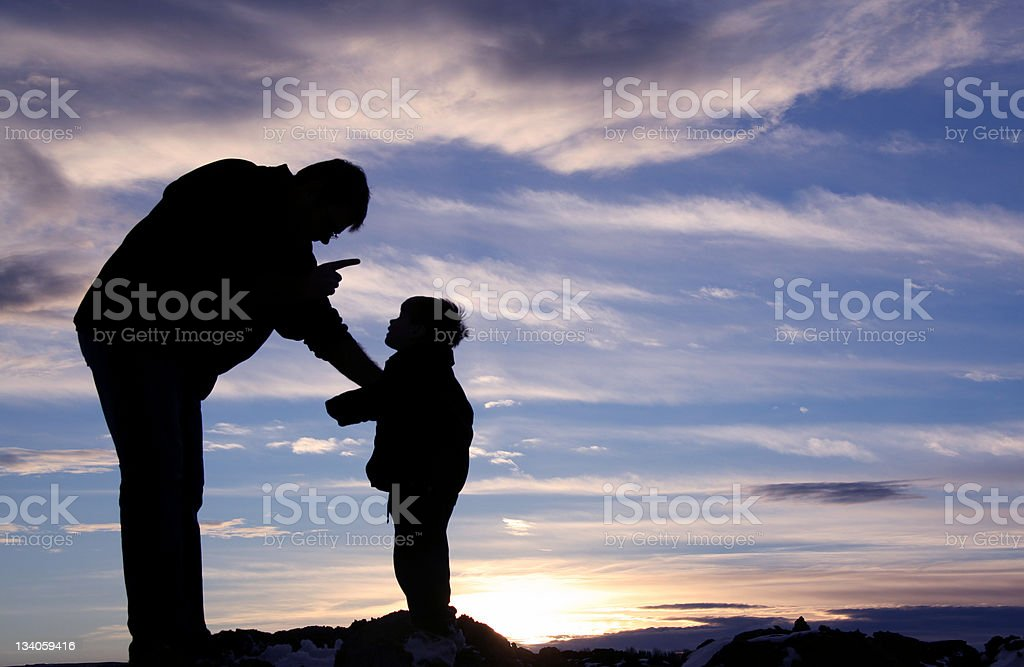 Silhouette of a Father Scolding His Child royalty-free stock photo