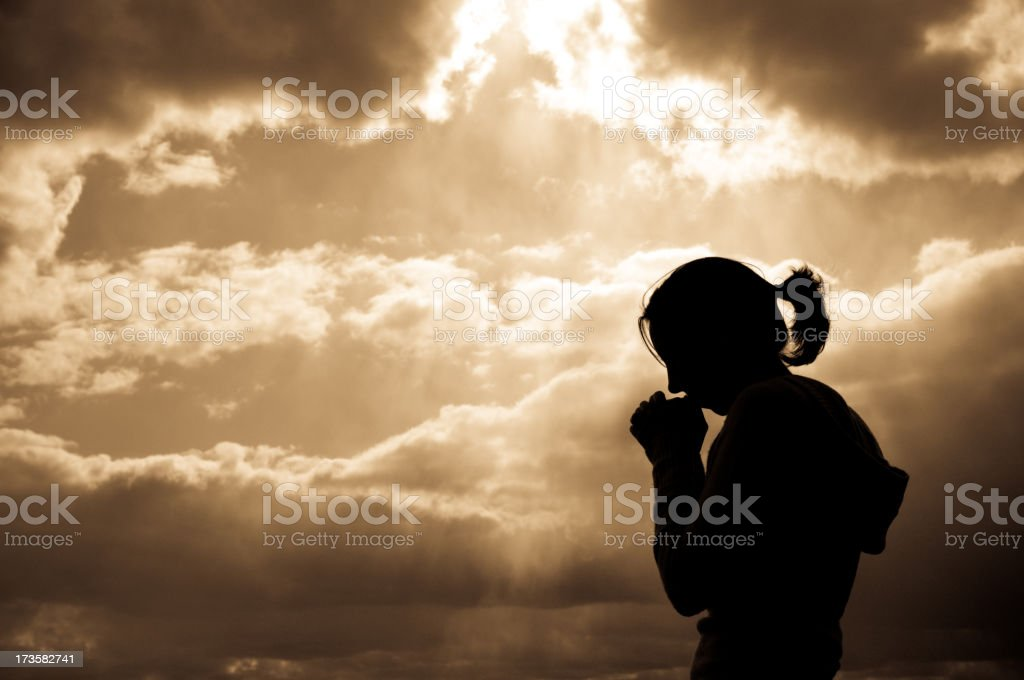 A silhouette of a female praying stock photo