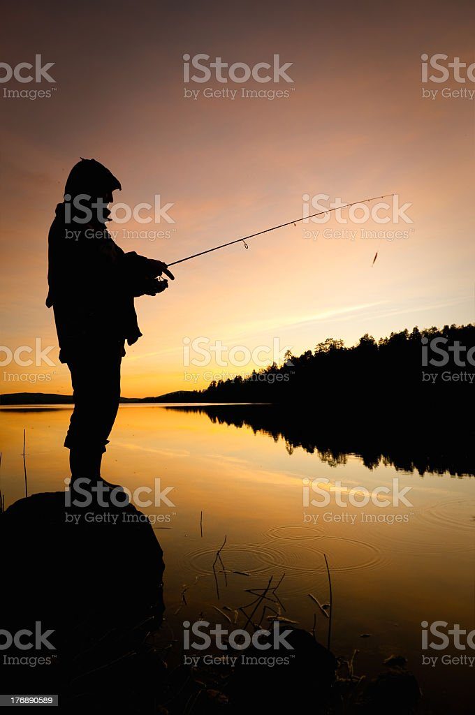 Silhouette of a fisherman at sunset royalty-free stock photo