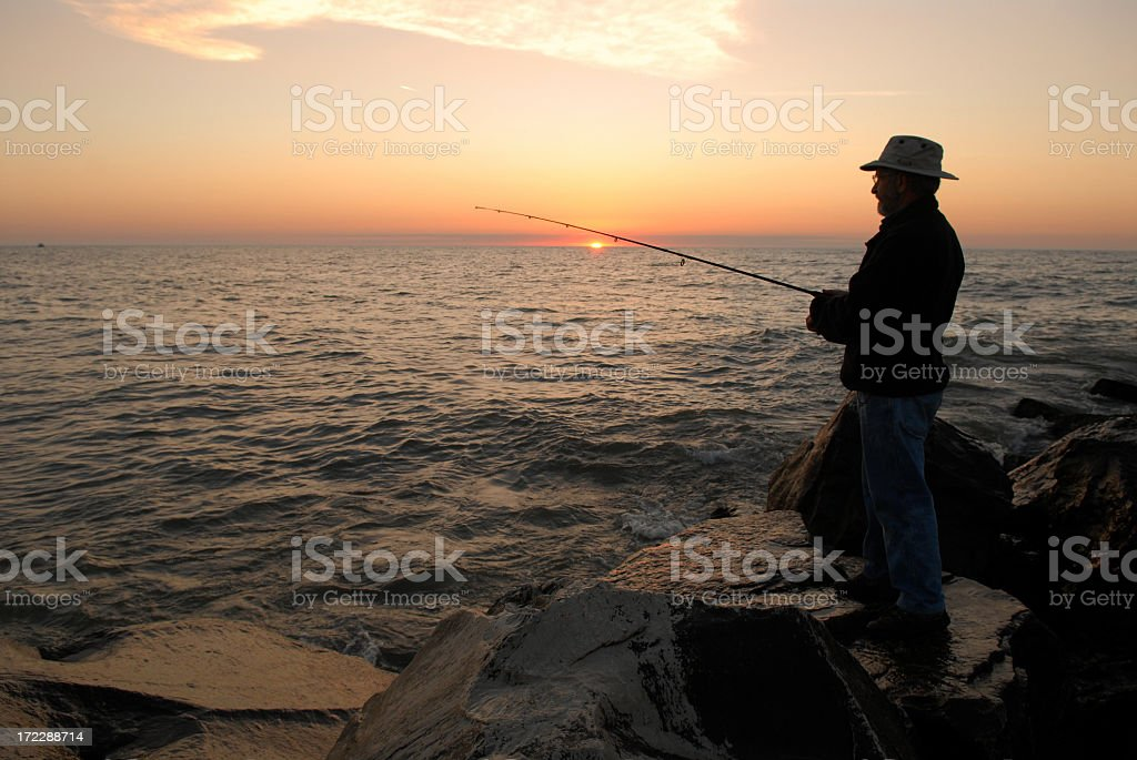 Silhouette of a fisherman during sunrise on Lake Michigan stock photo