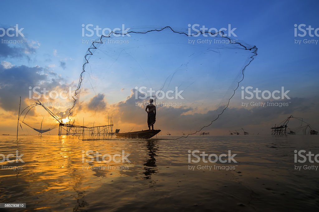Silhouette of a fisherman throwing his net with beautiful sky stock photo