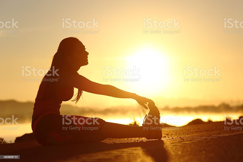 Silhouette of a fitness woman stretching at sunset stock photo