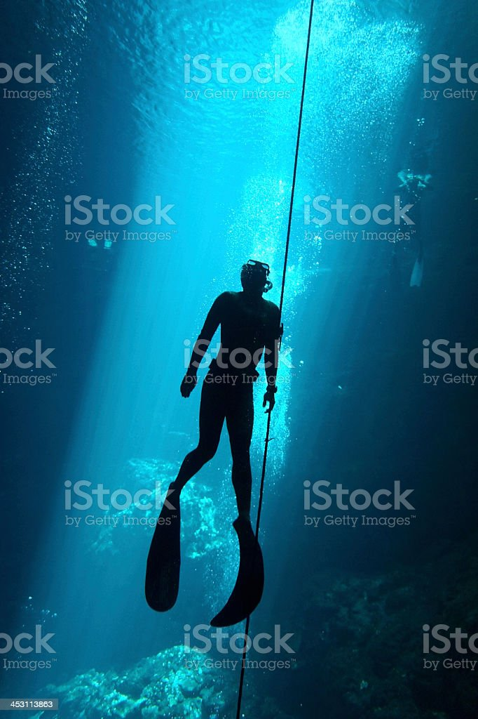 Silhouette of a free diver underwater stock photo