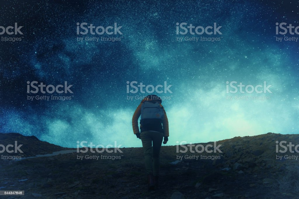Silhouette of a girl and mountain with stars. stock photo