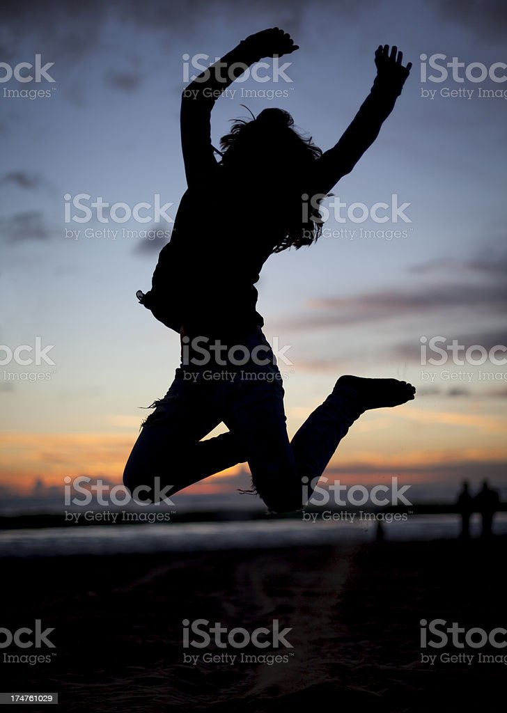 Silhouette of a girl jumping on beach at sunset stock photo